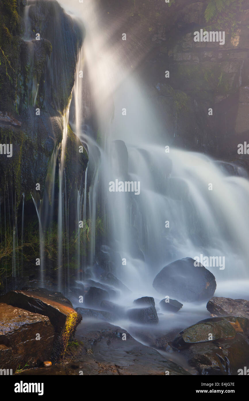 Rays of sunlight filtering onto rocks above East Gill Force Waterfall, Keld, Swaledale, Yorkshire Dales, UK Stock Photo