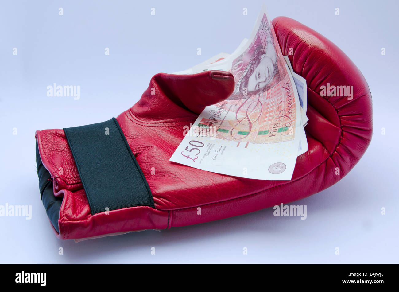 Red Boxing glove with pound notes on white background - Stock Image