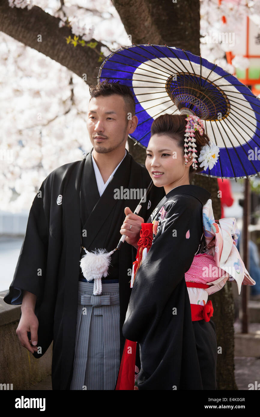Young couple in traditional wedding attire pose amid cherry blossoms in the Higashi Chaya district of Kanazawa - Stock Image