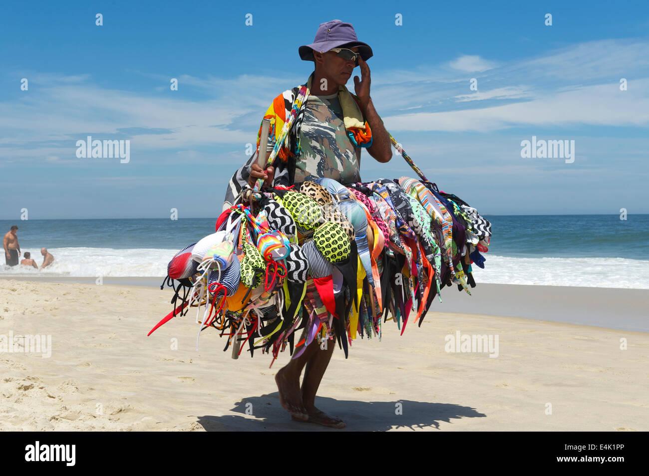 RIO DE JANEIRO, BRAZIL - MARCH, 2013: A beach vendor selling bikinis carries his merchandise along Ipanema Beach. - Stock Image