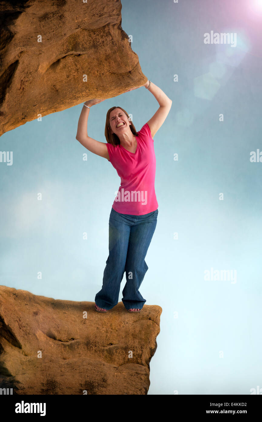 woman stressed and constrained trapped by a heavy weight - caught between a rock and a hard place or spot - Stock Image