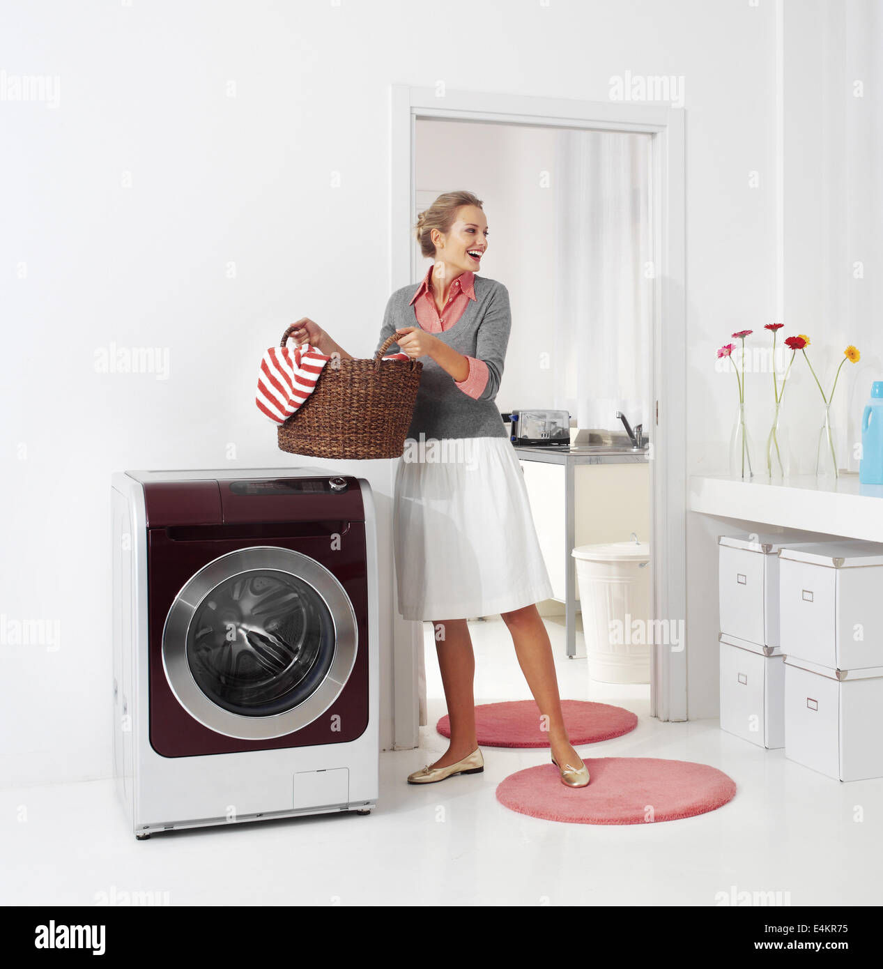 woman doing a housework holding basket of laundry - Stock Image