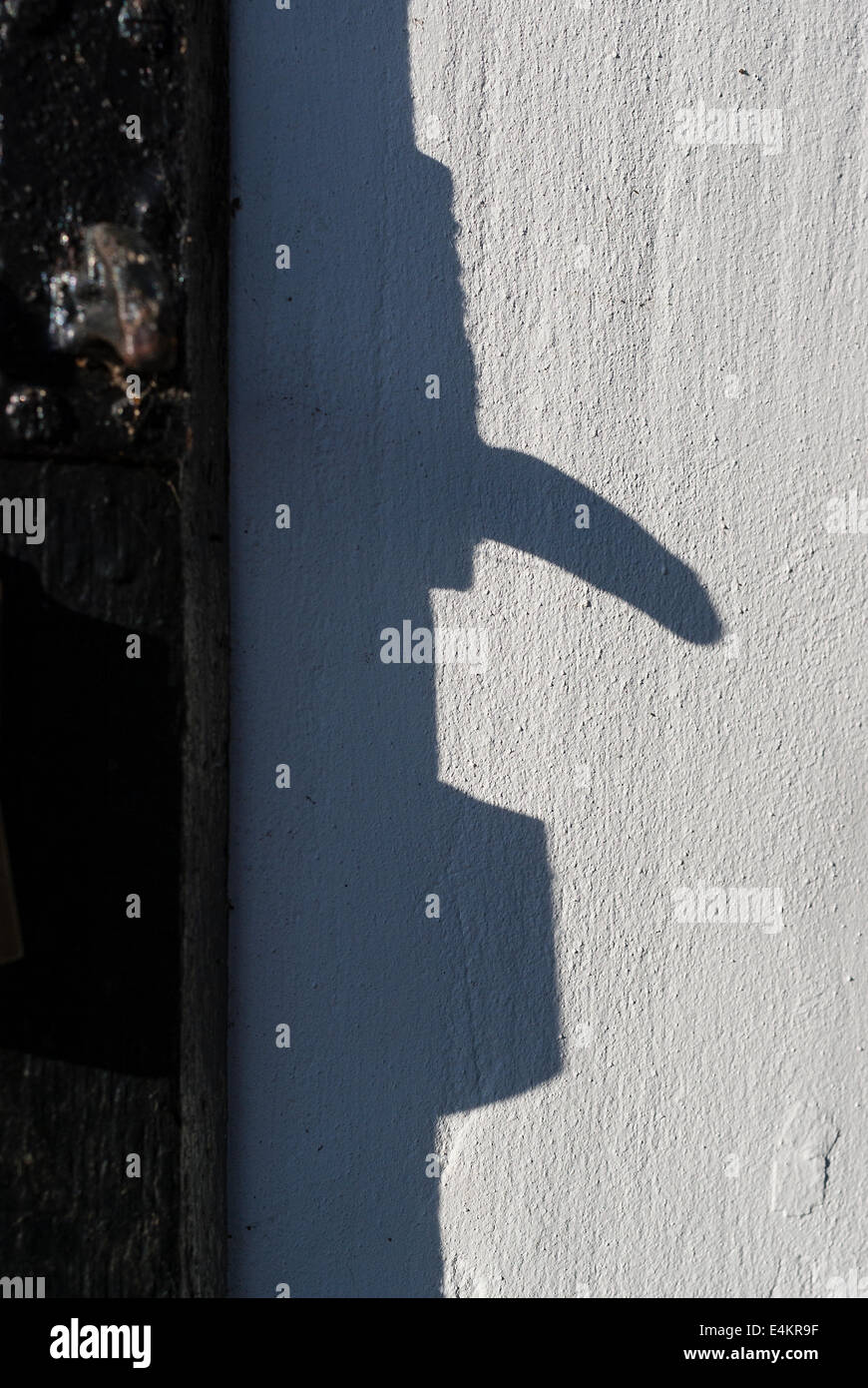 Nose-like shadow cast by old door handle - Stock Image