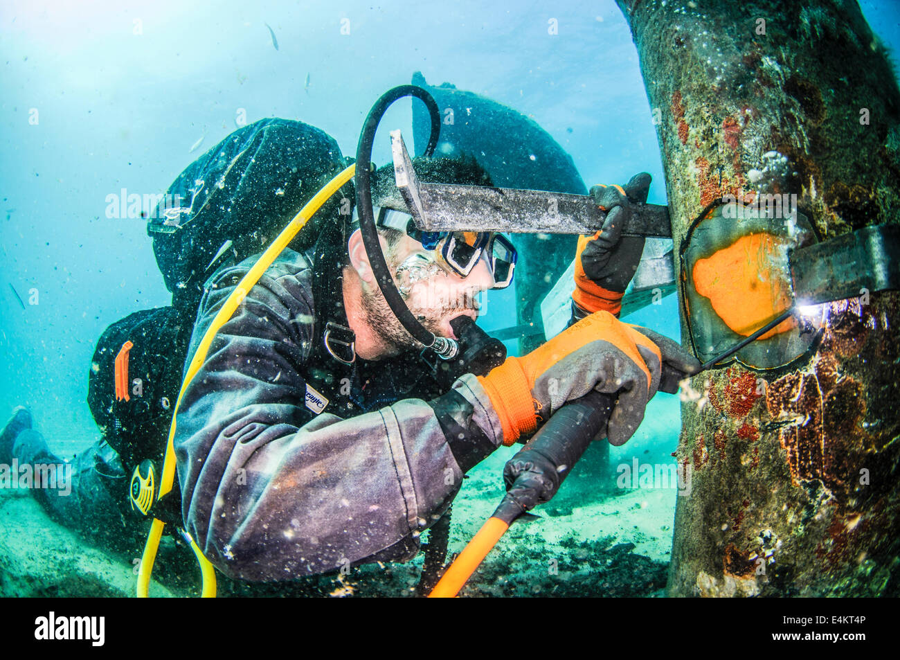 Commercial divers attach a zinc anode to a brine discharge pipe from a desalination plant on the seabed to a distance - Stock Image