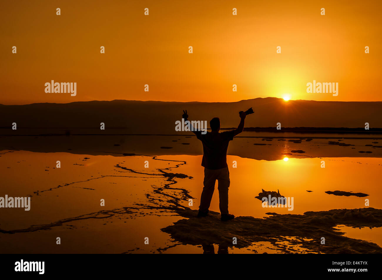 Silhouette of a man appreciating the sunrise Photographed at the Dead Sea Israel - Stock Image