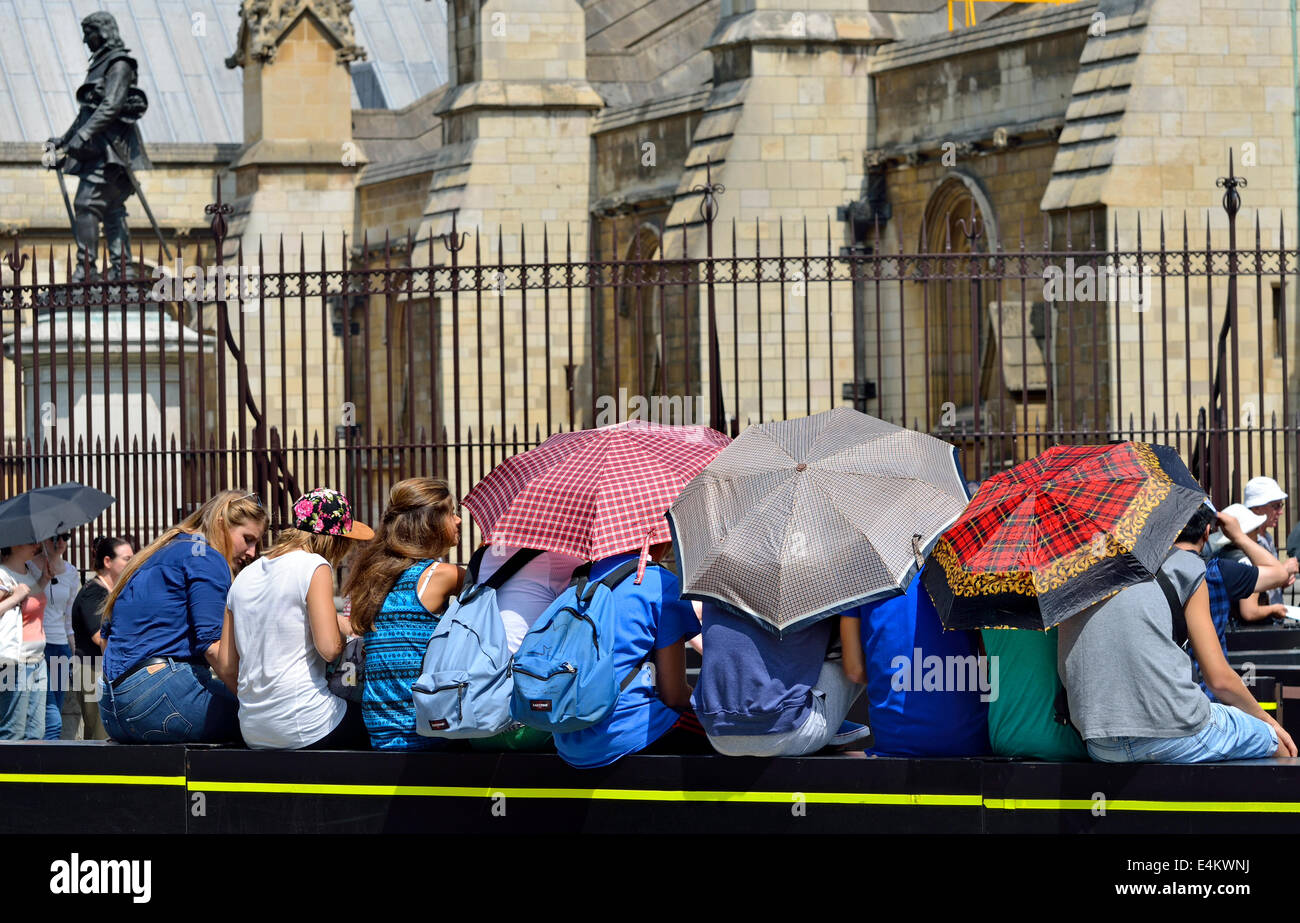 London, England, UK. Tourists sheltering from the sun by the Houses of Parliament - Stock Image