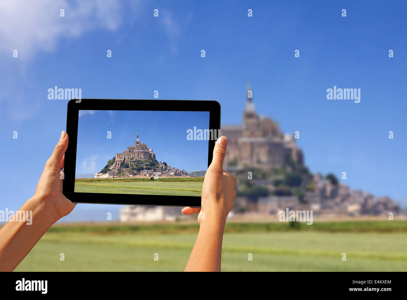 Girl taking pictures on a tablet, Le Mont Saint Michel Abbey, Normandy / Brittany, France - Stock Image