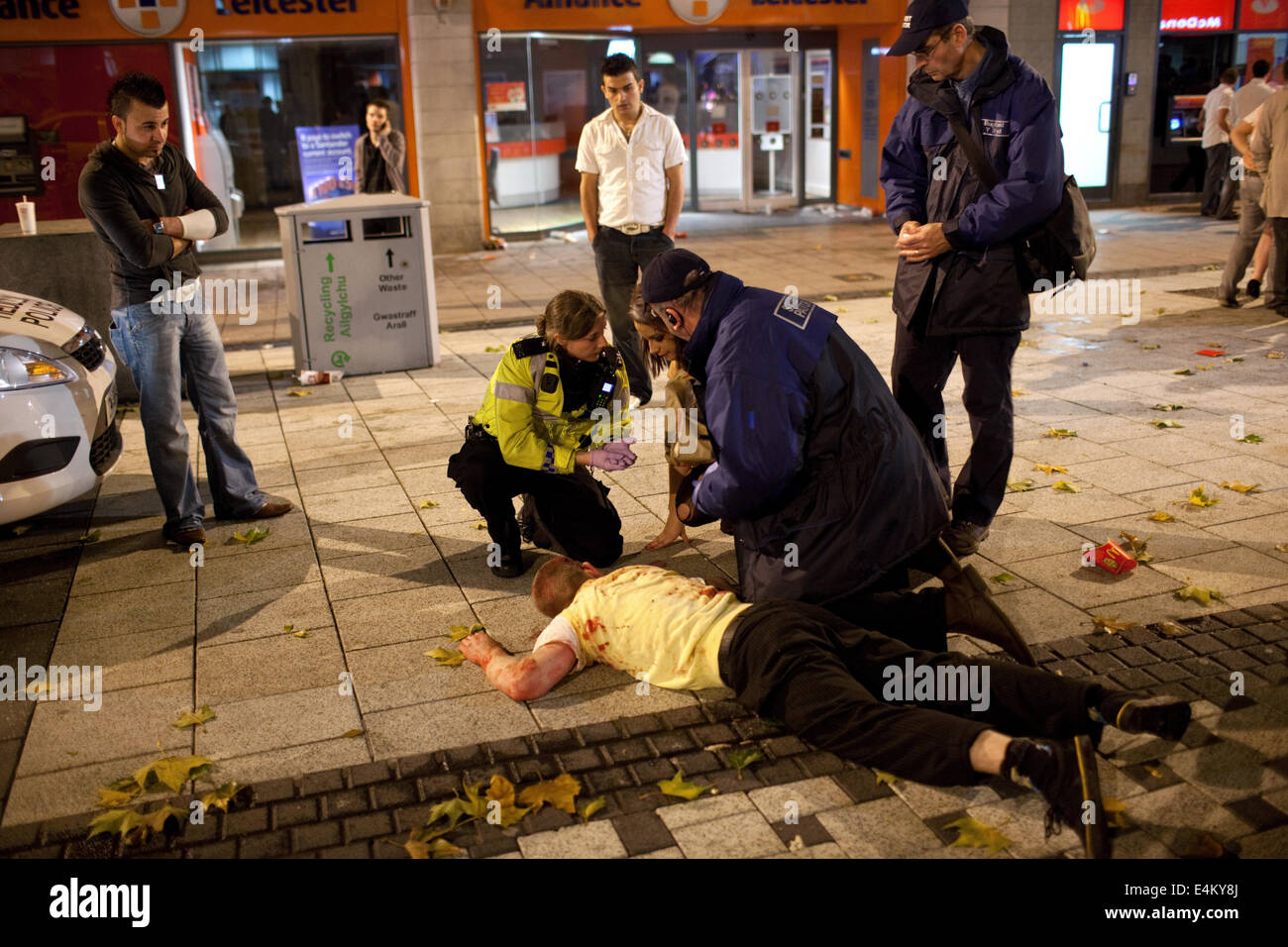 Street Pastors and Police taking care of a young man injured in a fight on a weekend night in Cardiff, Wales, UK - Stock Image