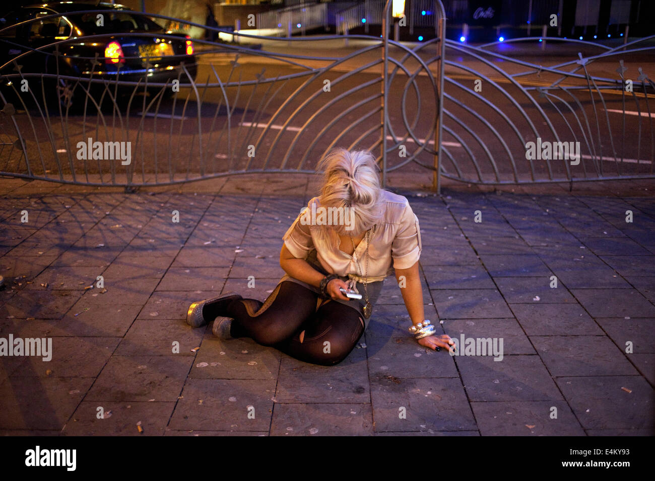 A young drunk woman sitting on a pavement ans texting sms on her mobile  phone on