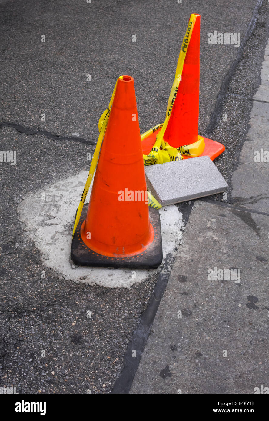 Traffic cones set up to protect repair work on a New York City sidewalk - Stock Image