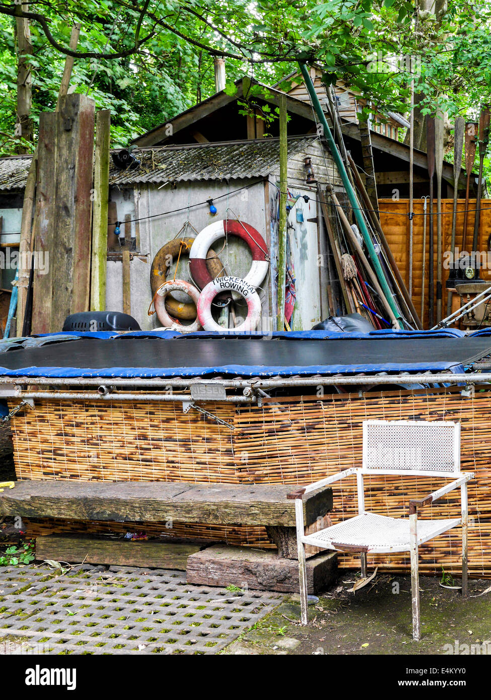 Old chair, bench and life belts near artist's studios in the working boatyard on Eel Pie Island. Twickenham - Stock Image