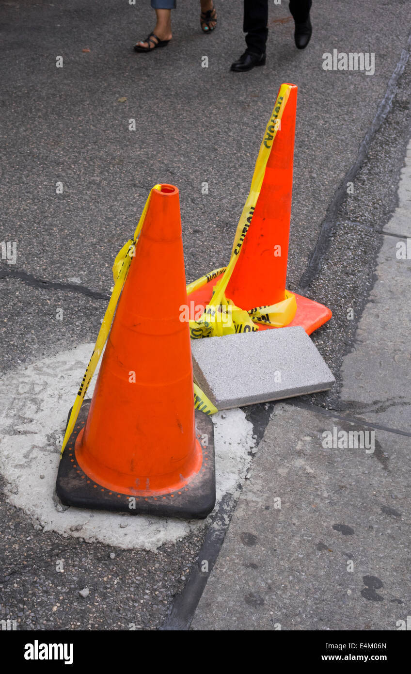 Traffic cones set up to protect repair of sidewalk in New York City - Stock Image