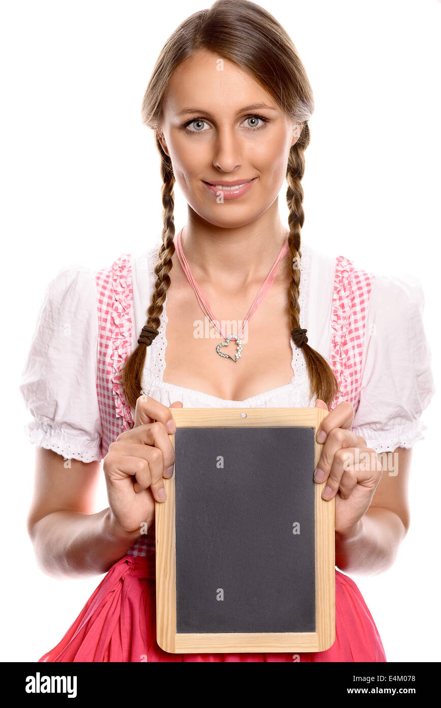 Young woman in a dirndl holding up a blank slate - Stock Image