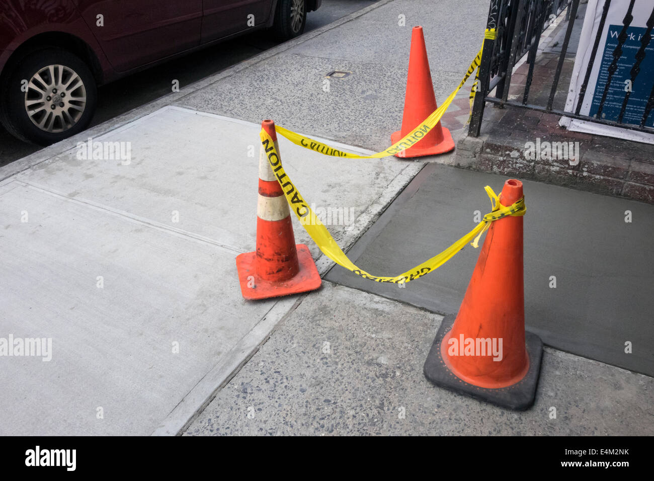 Traffic cones calling attention to an area of repair to a New York sidewalk - Stock Image