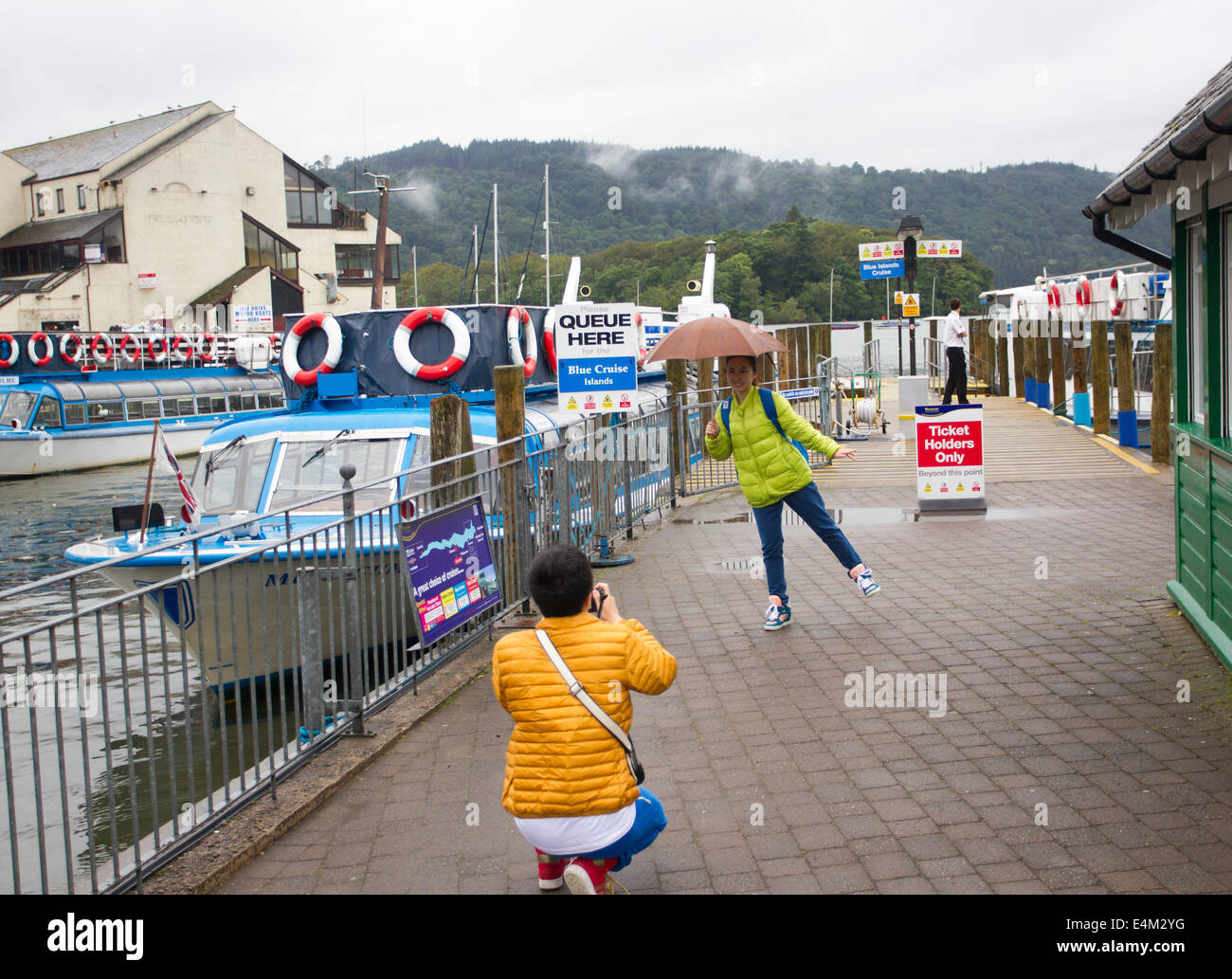 Bowness on Lake Windermere, UK. 14th July, 2014. Tourists making the most of a rainy day Japanese tourists have fun posing in the rain Credit:  Gordon Shoosmith/Alamy Live News Stock Photo