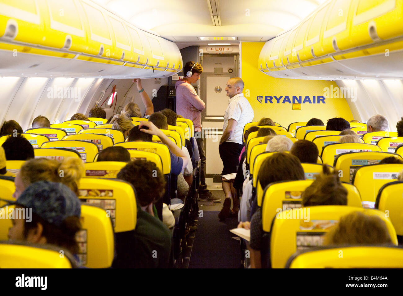 Passengers in a queue for the toilet during a flight, Ryanair plane cabin interior - Stock Image