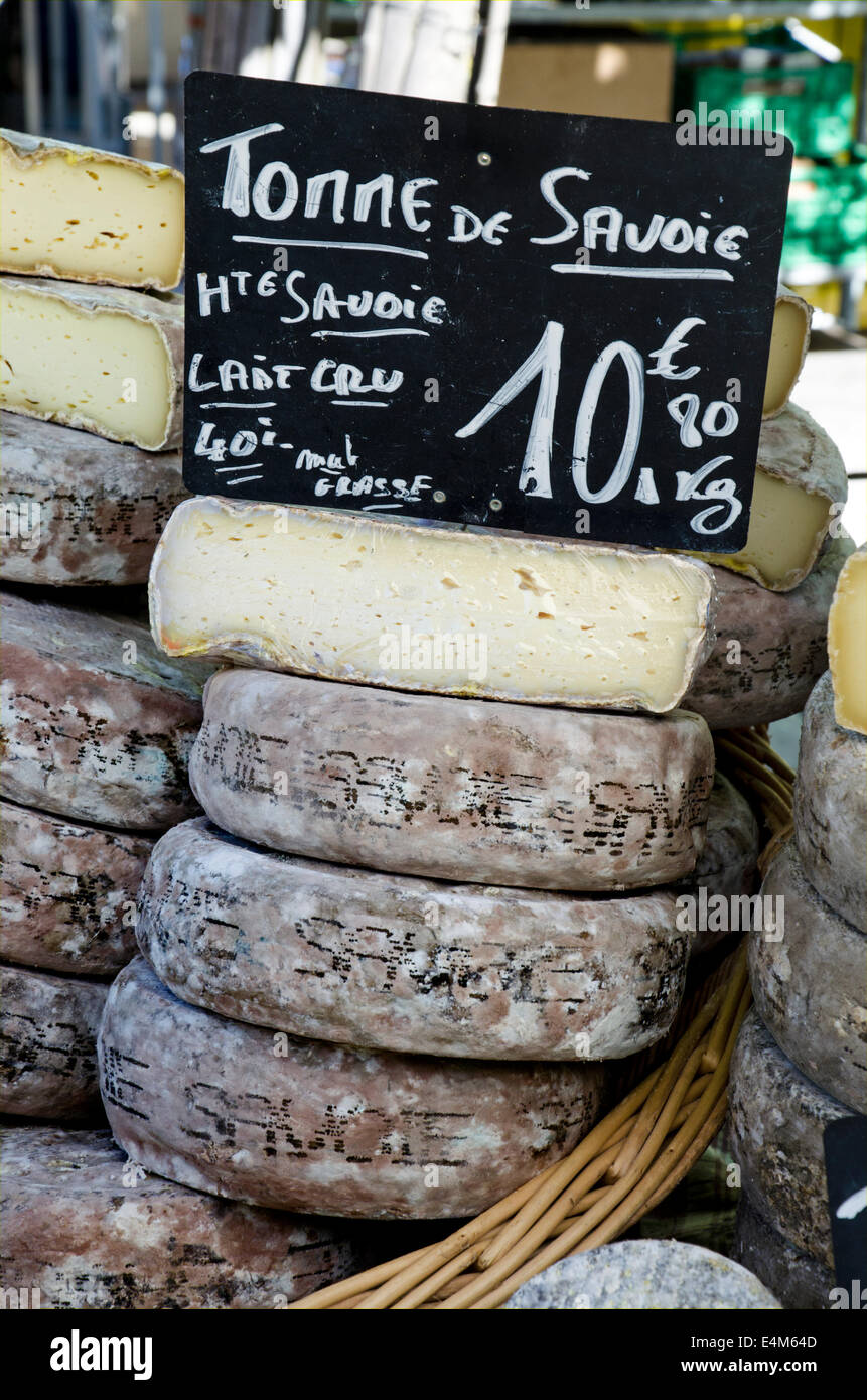 Tomme de Savoie on a market stall at the Saturday market in Chamonix, Haute Savoie, France. - Stock Image