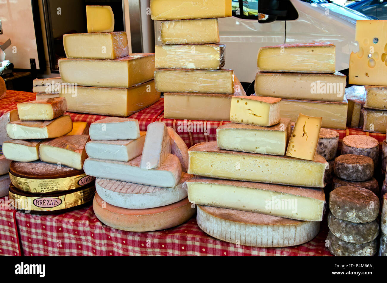 A selection of cheeses on a market stall at the Saturday market in Chamonix, Haute Savoie, France. - Stock Image
