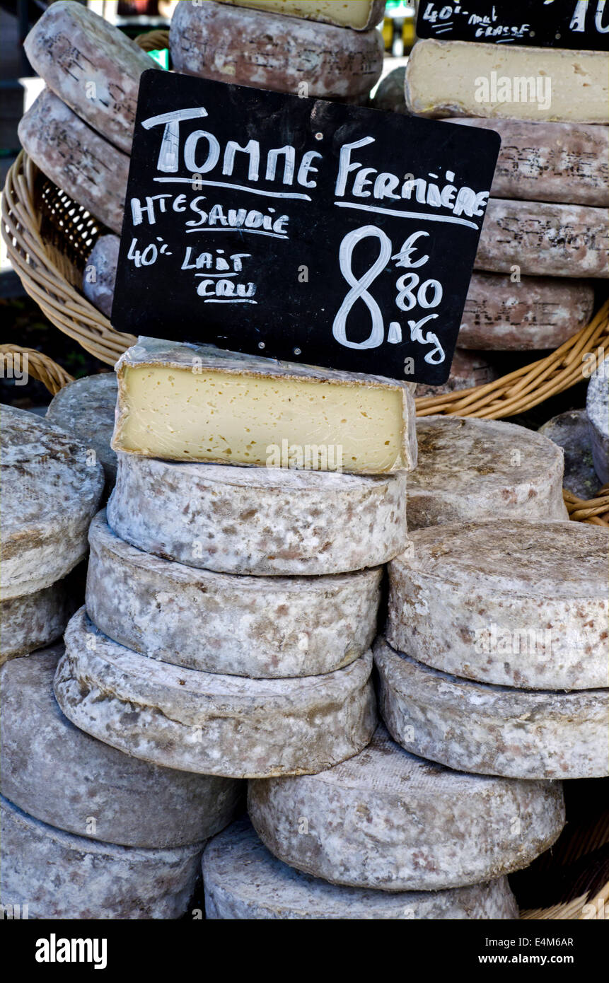 Tomme Fermiere on a market stall at the Saturday market in Chamonix, Haute Savoie, France. - Stock Image