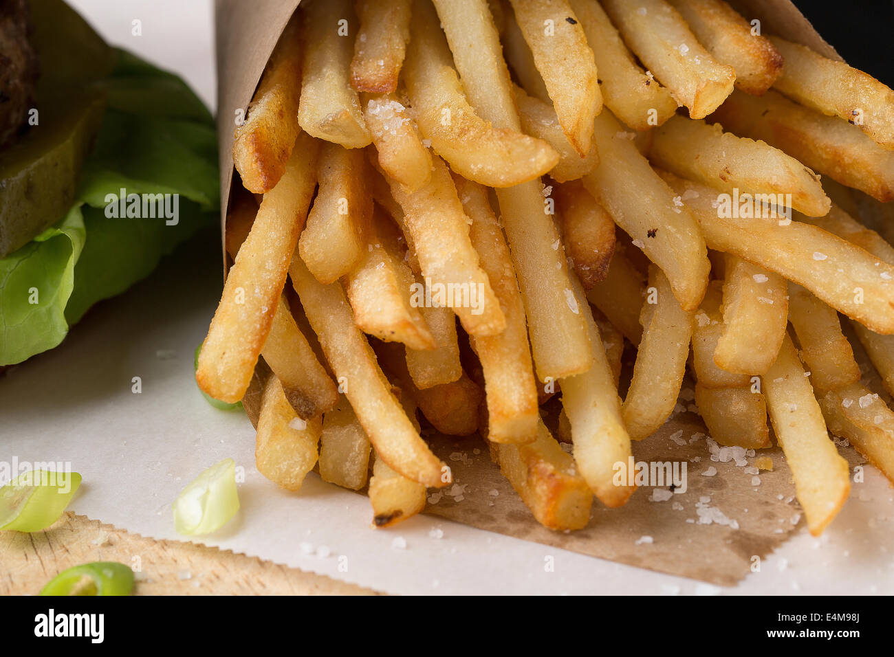 French Fries close up with pickle & lettuce detail from burger. - Stock Image