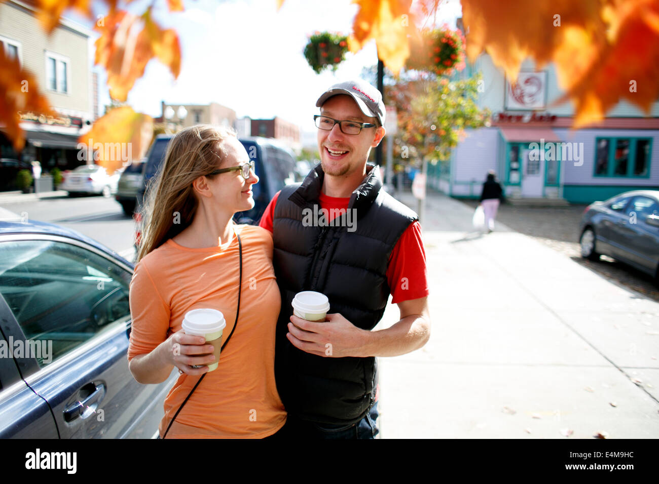 Couple Holding Coffee Cups on Sidewalk - Stock Image