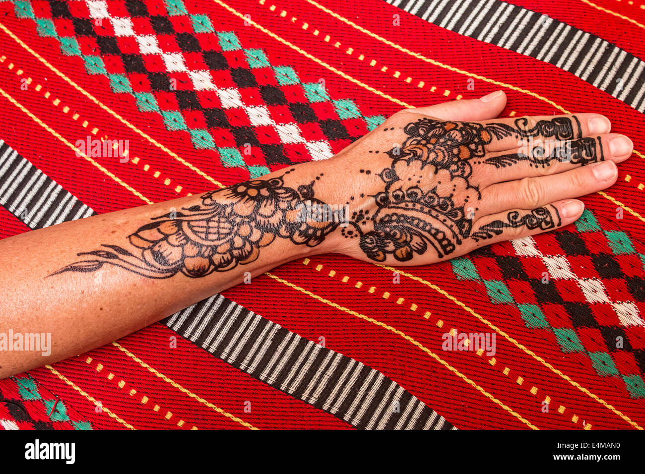 Colorful and intricate henna tattoo on a woman's hand and arm. This is a popular decoration for women in the - Stock Image