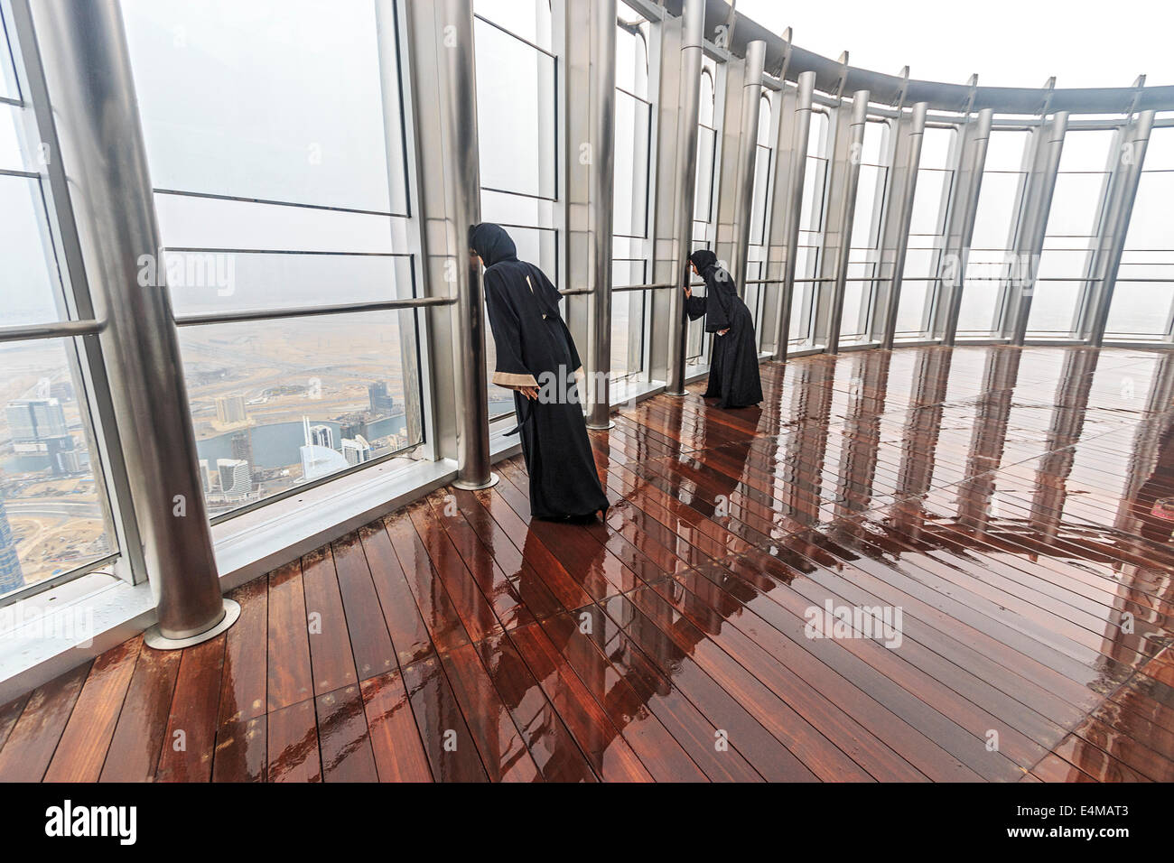 Local Muslim women wearing traditional burka robes have fun posing at the observation deck of the Burj Khalifa - Stock Image