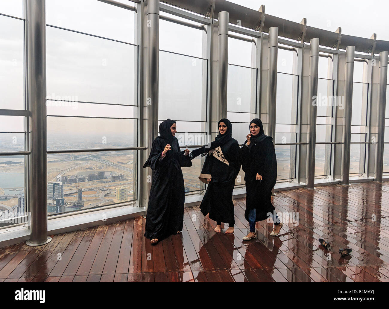 Local women wearing traditional Muslim burka robes arrive to view the city of Dubai from the top of the Burj Khalifa - Stock Image