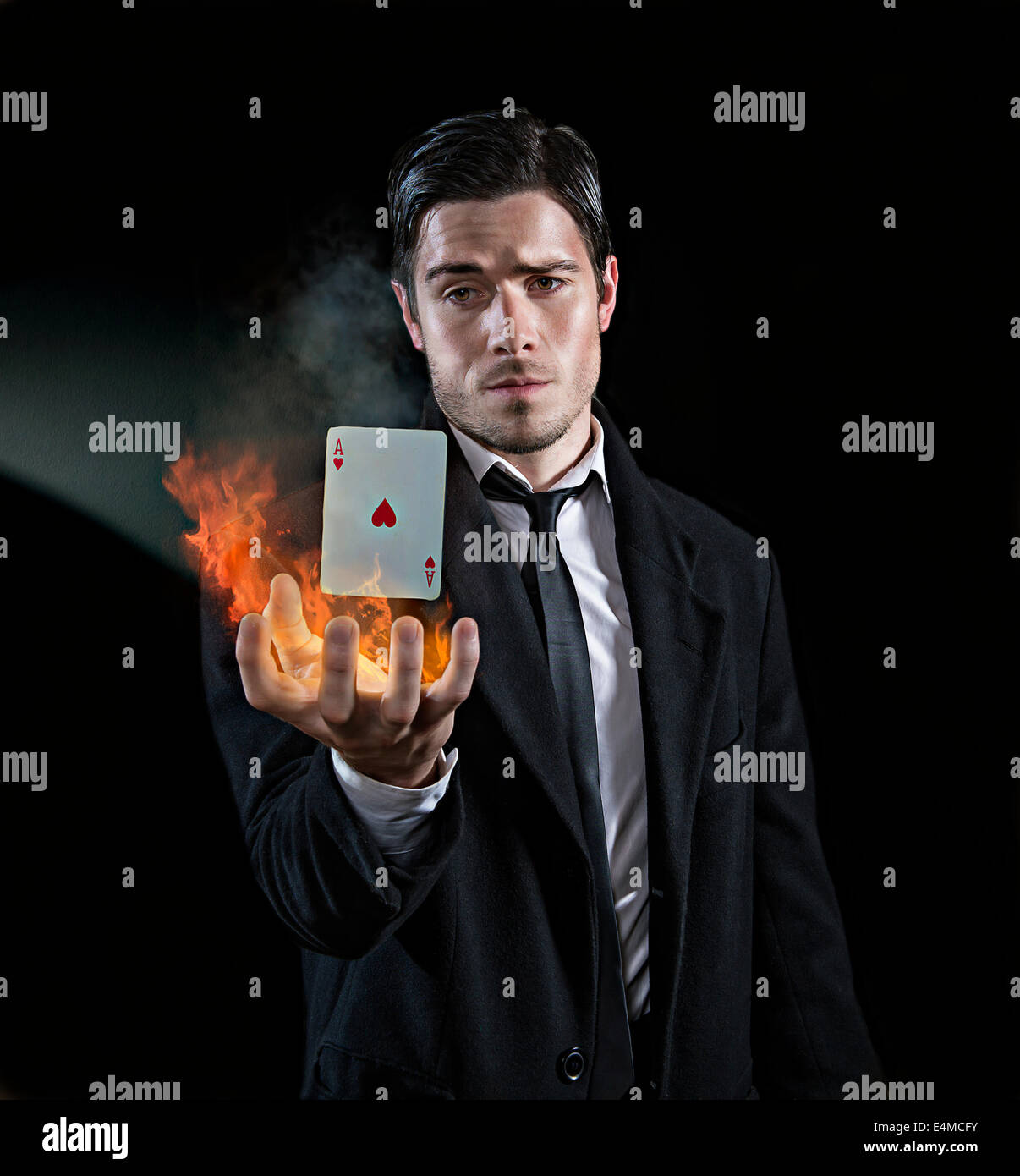 Magician produces an ace in flames - Stock Image