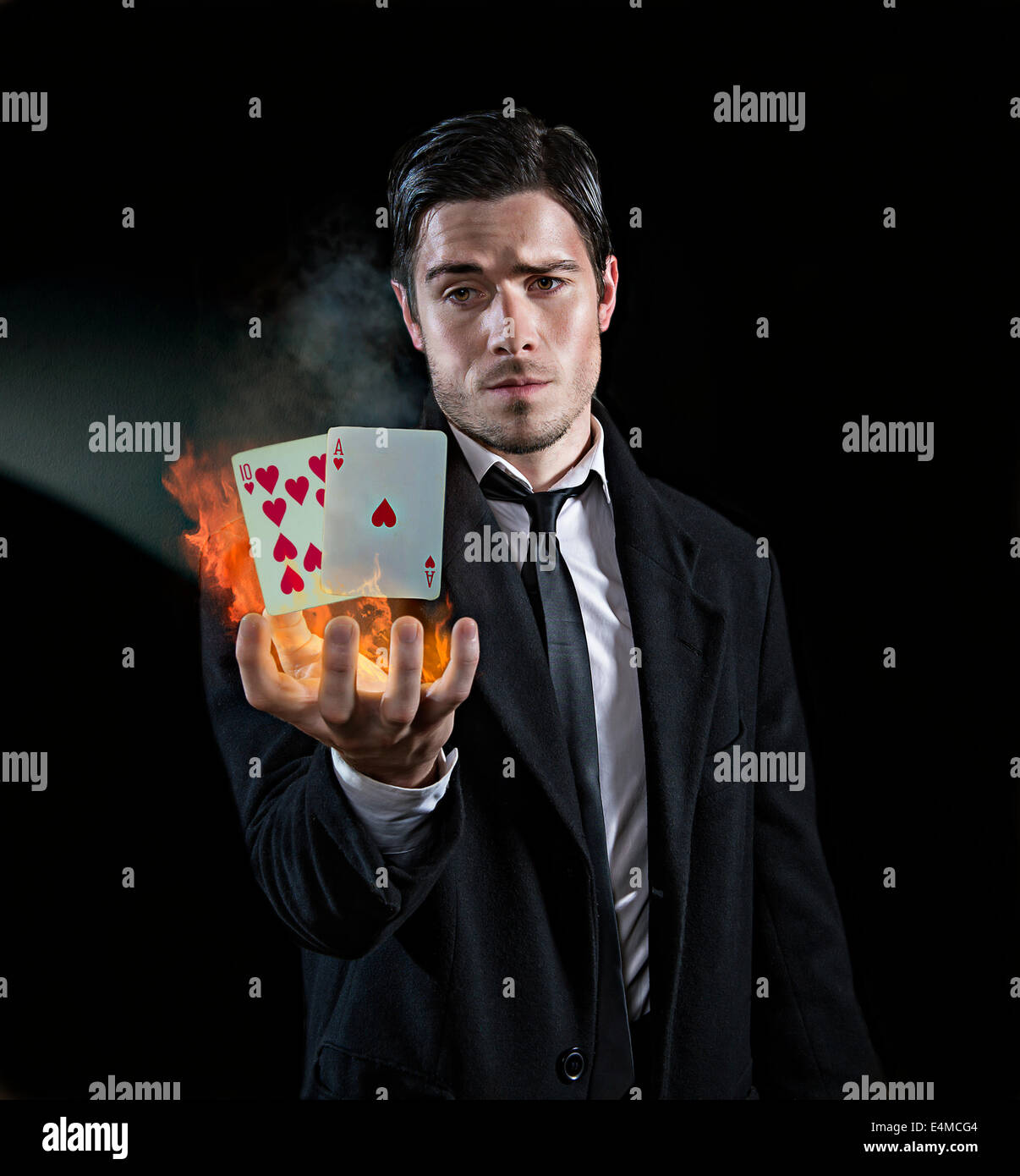 Magician producing black jack - Stock Image