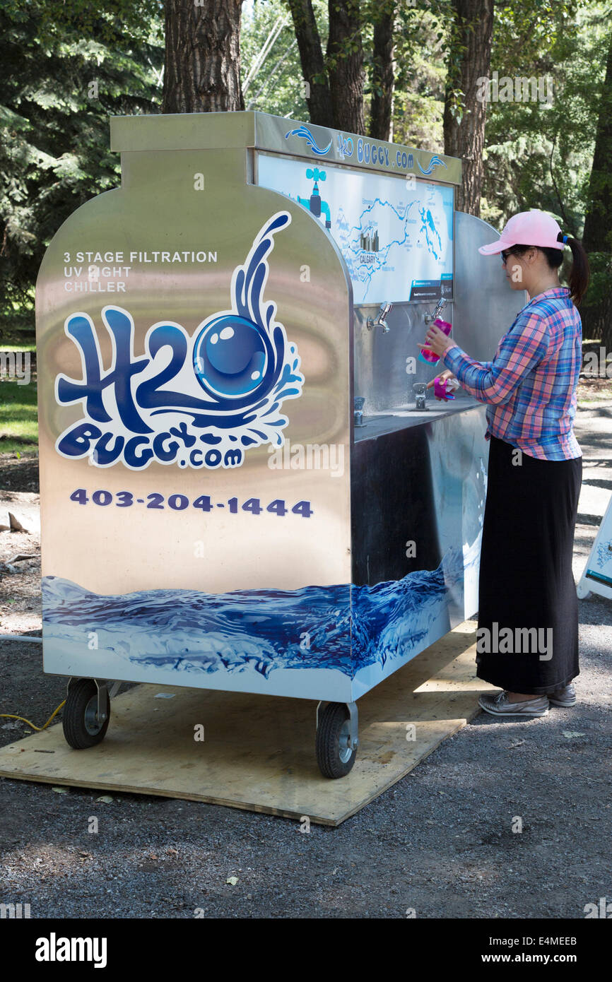 Woman filling reusable water bottle with drinking water from H2O buggy (mobile water station) at event in city park - Stock Image