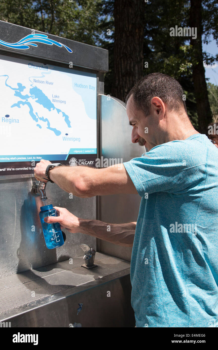 Man filling reusable water bottle from H2O buggy (mobile water station) at event in city park - Stock Image