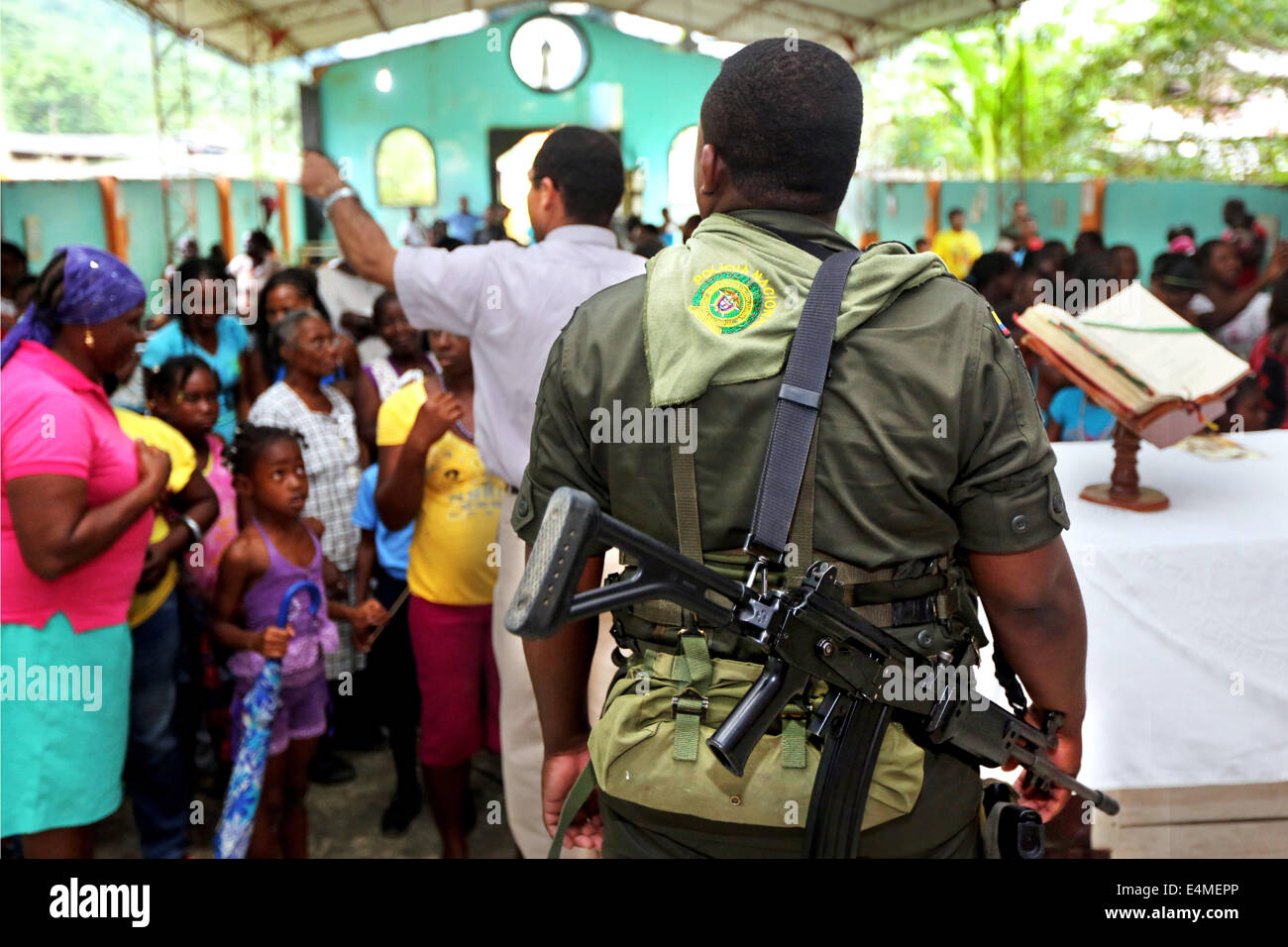 Heavily armed national policeman guarding behind the altar after a mass service in a church in Choco Province, Colombia Stock Photo