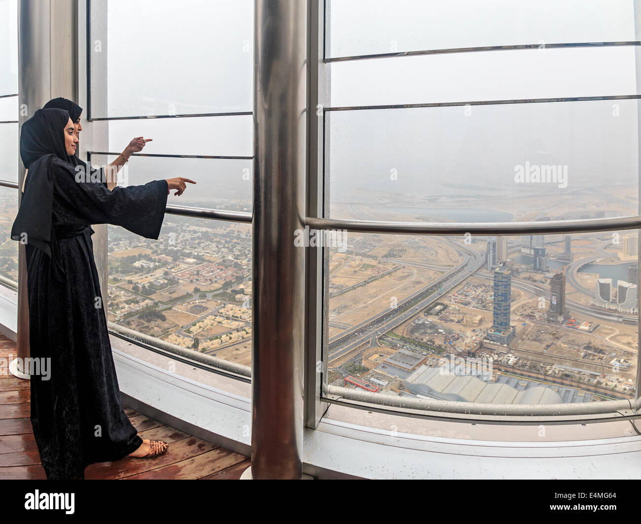Local women wearing traditional Muslim burka robes view the city of Dubai from the top of the Burj Khalifa - Stock Image