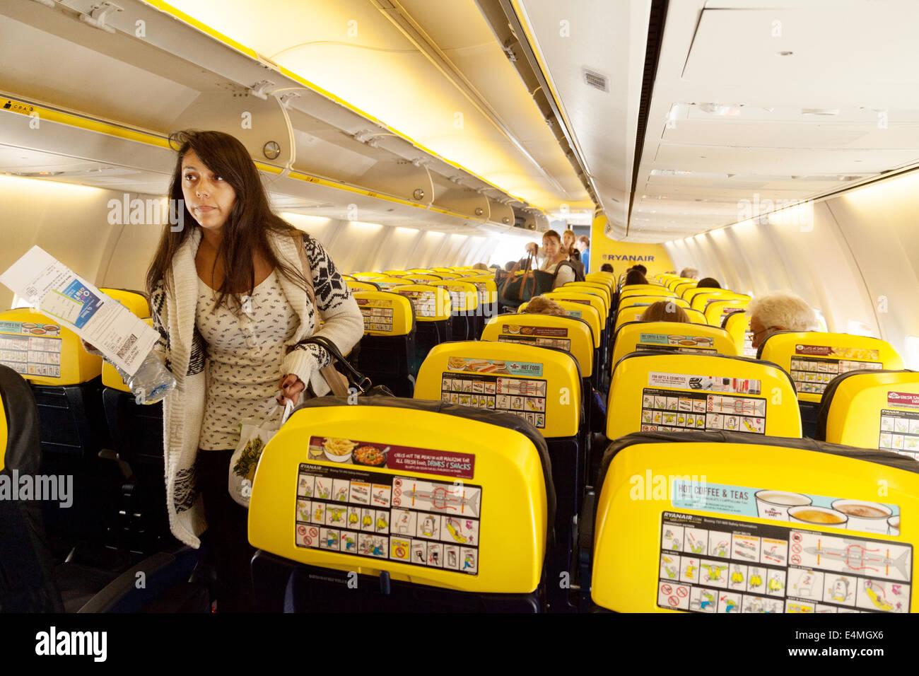 Passengers finding their seats, Ryanair plane cabin interior - Stock Image