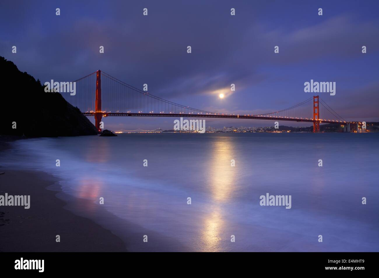 A full moon rises over San Francisco and the Golden Gate Bridge from Kirby Cove in the Marin Headlands. - Stock Image