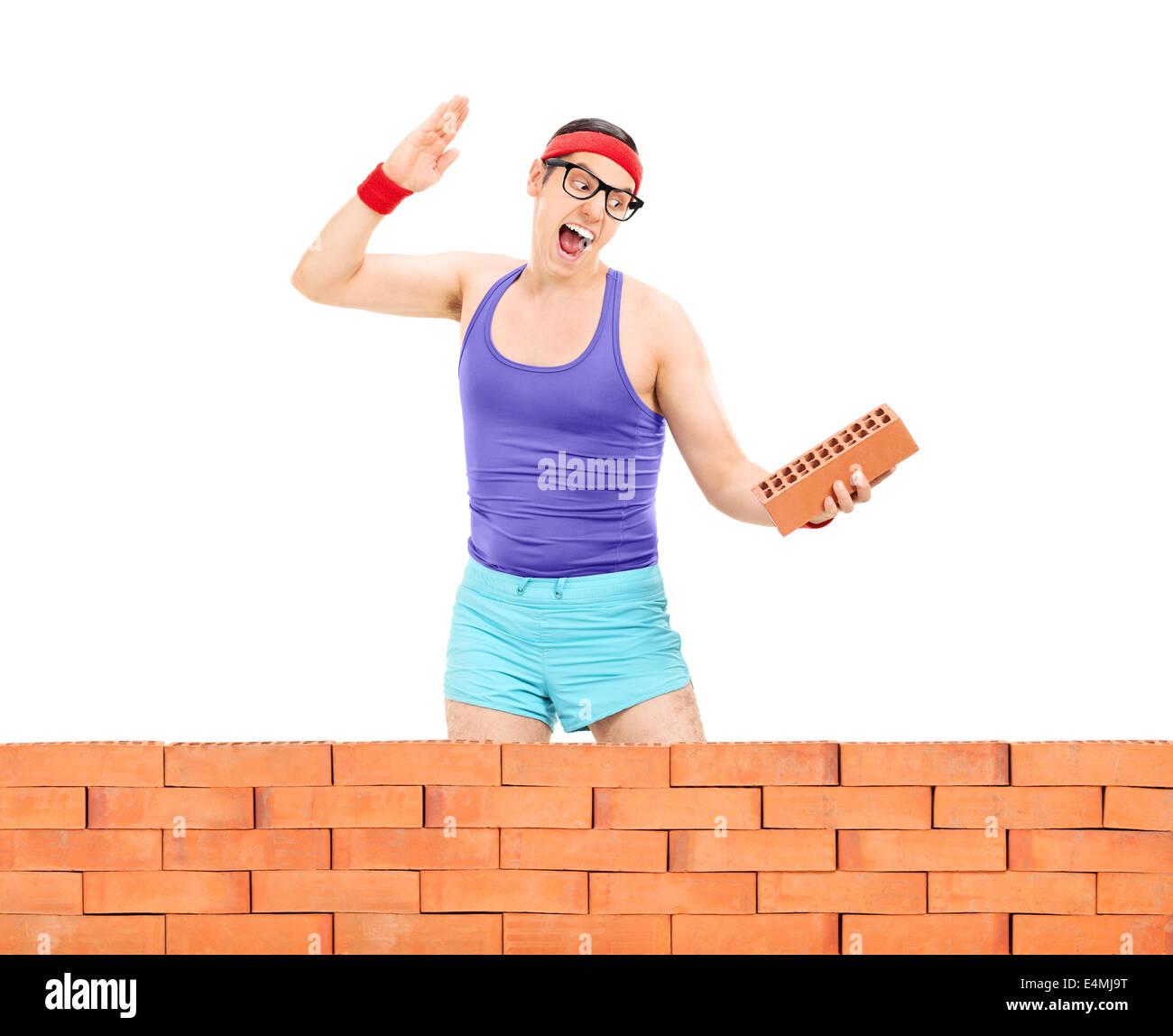 Man smashing a brick behind a brick wall - Stock Image