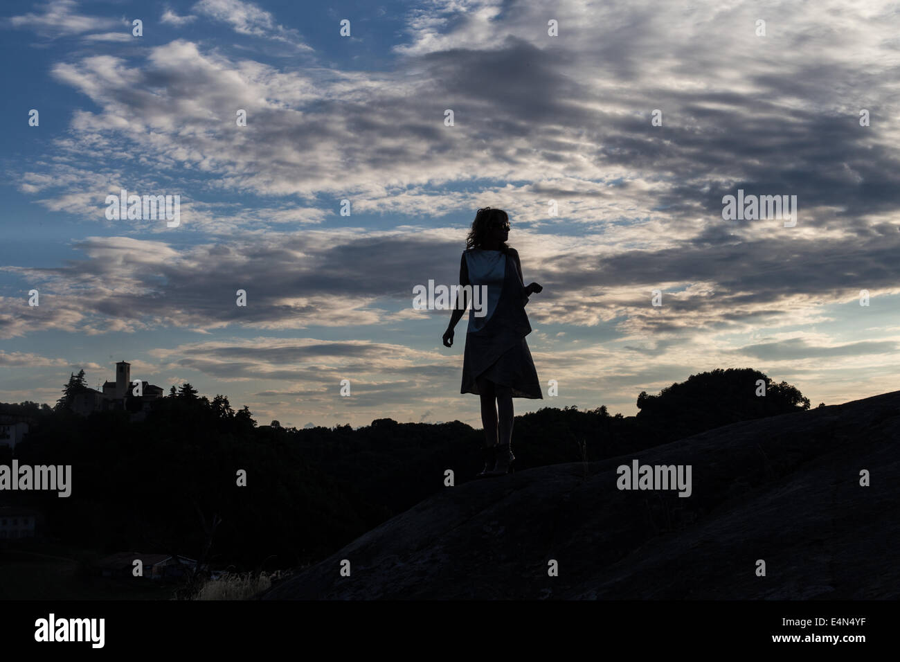 silhouette of a woman lost at sunset in a dress holding a bag with clouds in the background - Stock Image
