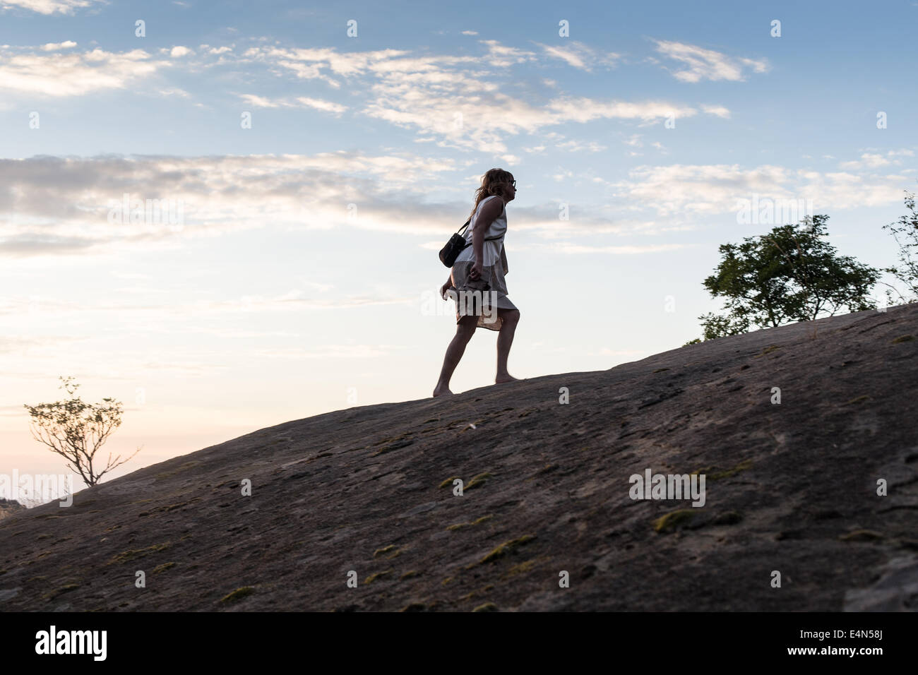 woman wearing dress walking up hill holding shoes in hands as the sun goes down - Stock Image