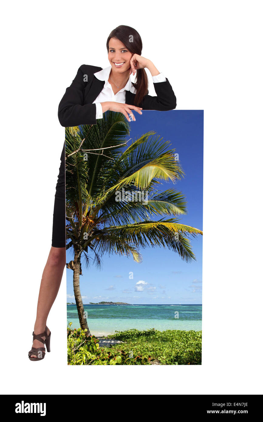 Agent with a poster of a tropical beach - Stock Image