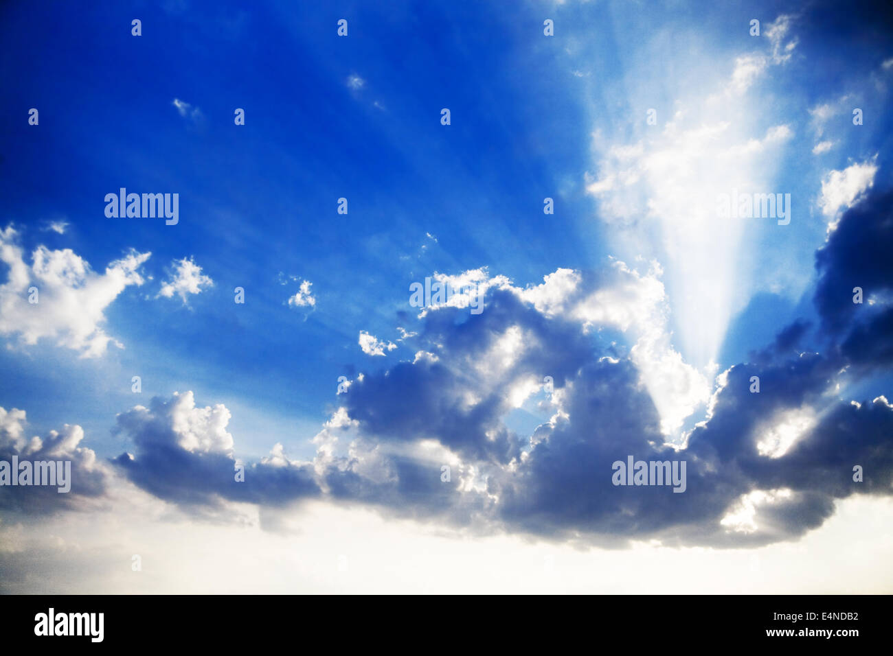 blue cloudy sky and bright sun beams - Stock Image
