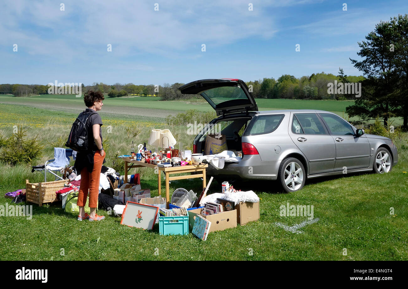 Young woman looking for bargain on car boot sale in Swedish countryside. - Stock Image
