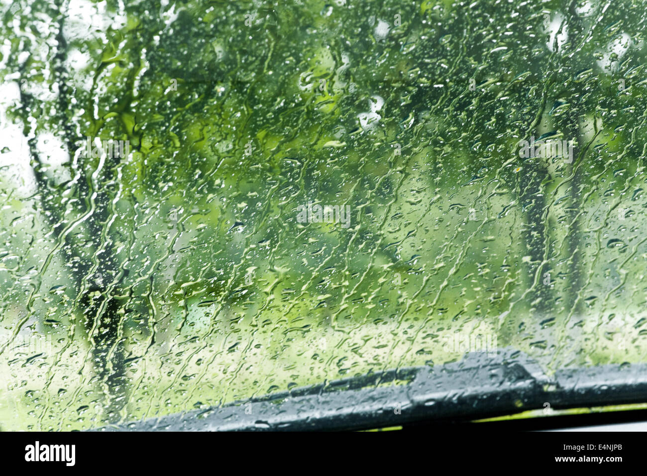 raindrops roll down a car windshield - Stock Image
