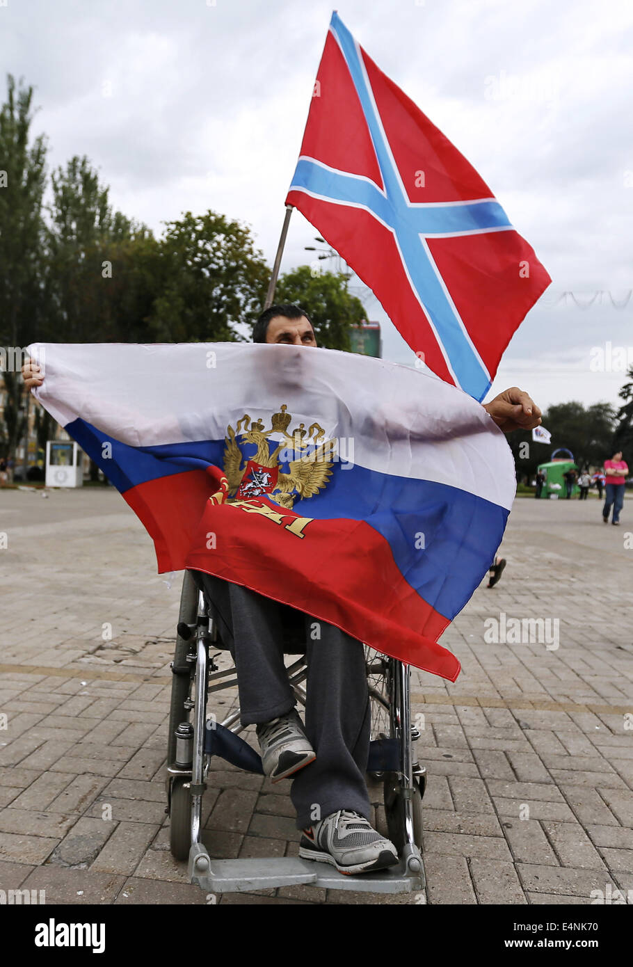 Donetsk, Ukraine. 13th July, 2014. A man in a wheelchair holds a Russian flag ahead of a rally marking the 250th - Stock Image