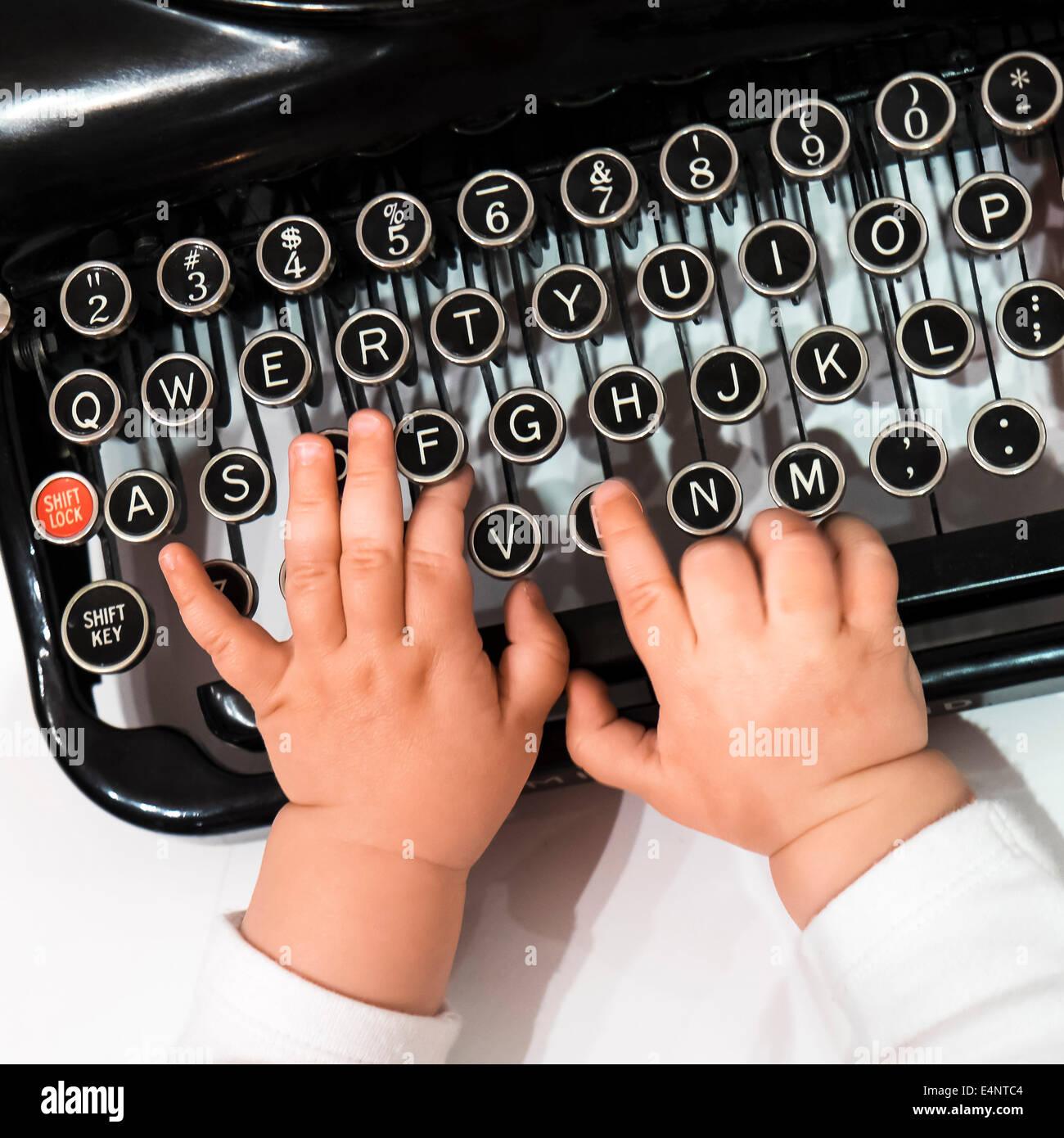 Studio shot of babies (6-11 months) hand touching typewriter - Stock Image