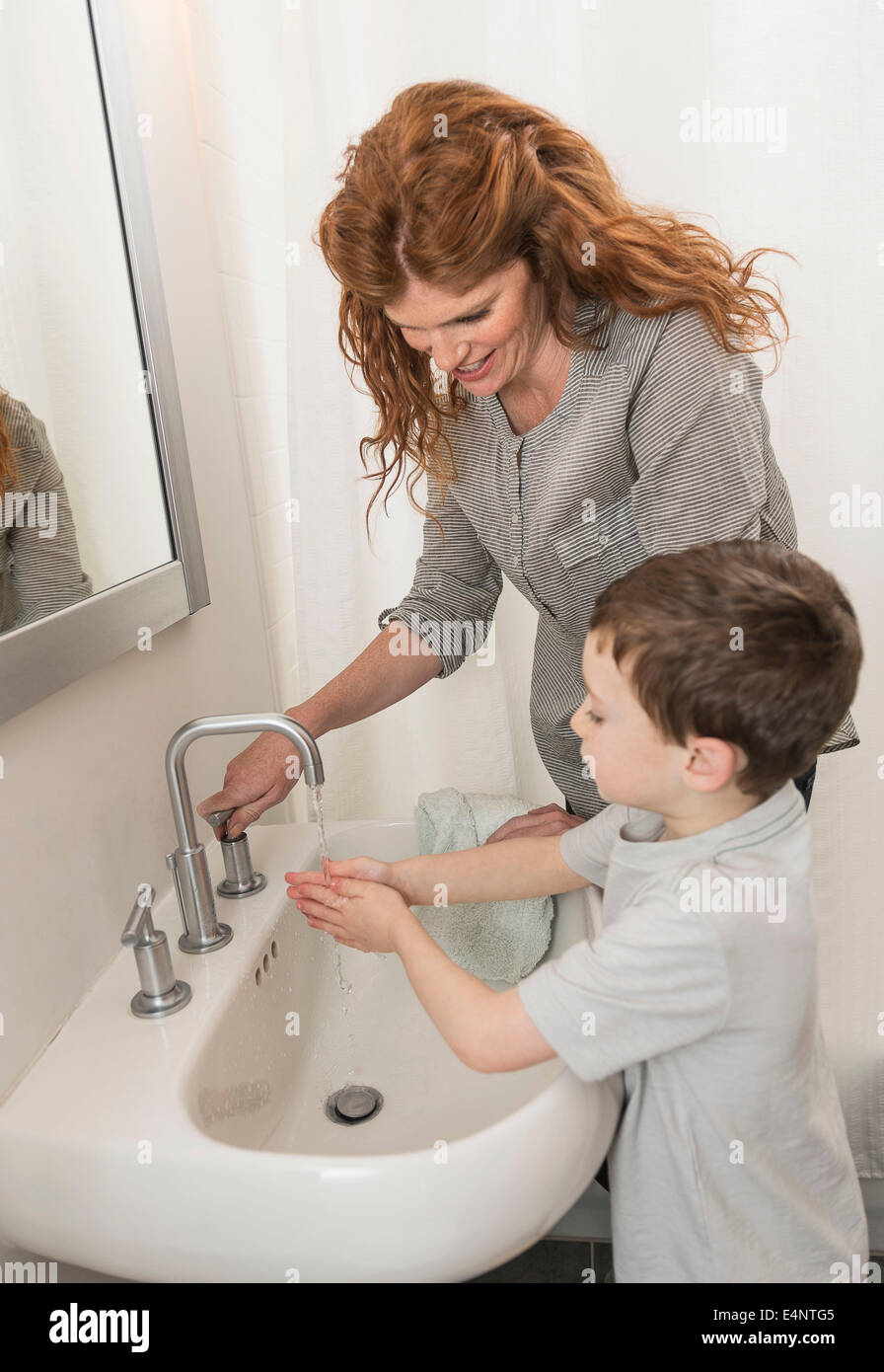Son (6-7) and mother washing hands - Stock Image