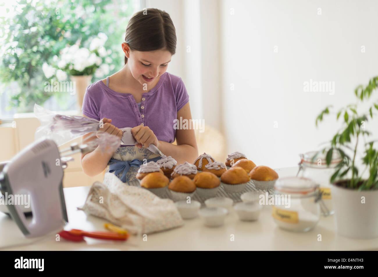 Girl (10-11) decorating cakes - Stock Image