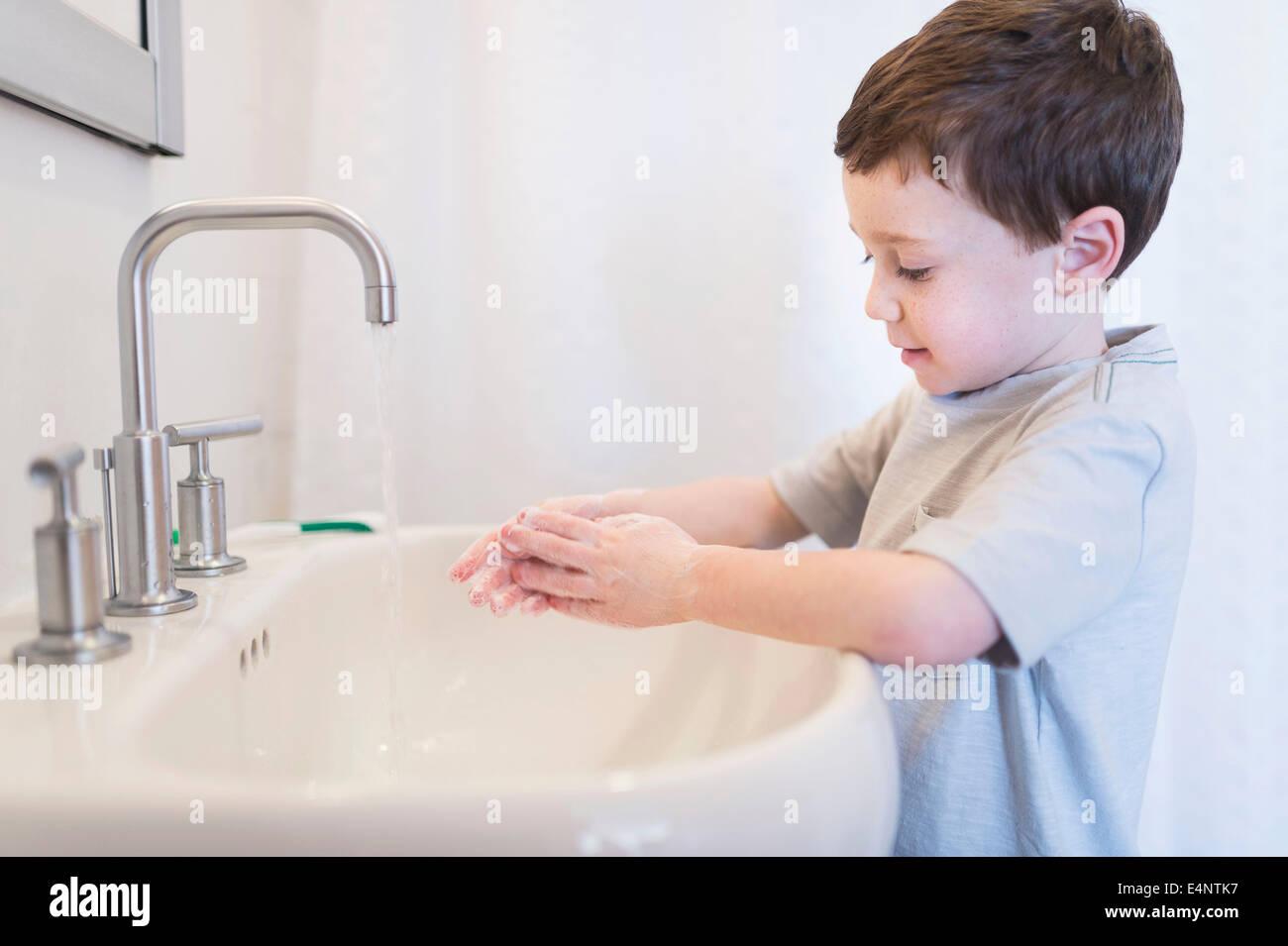 Boy (6-7) washing hands - Stock Image