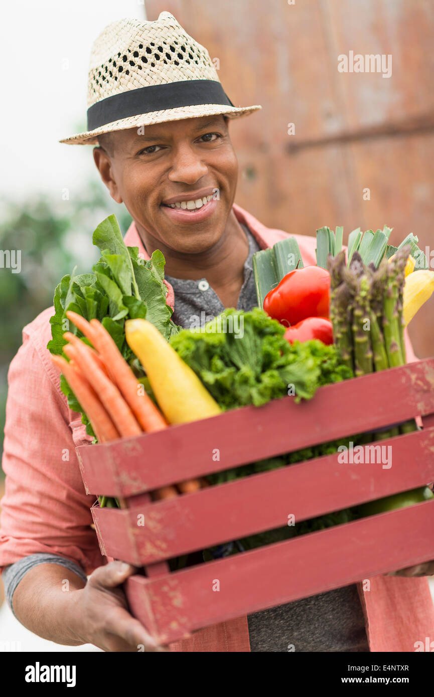 Portrait of man carrying crate full of fresh vegetables Stock Photo
