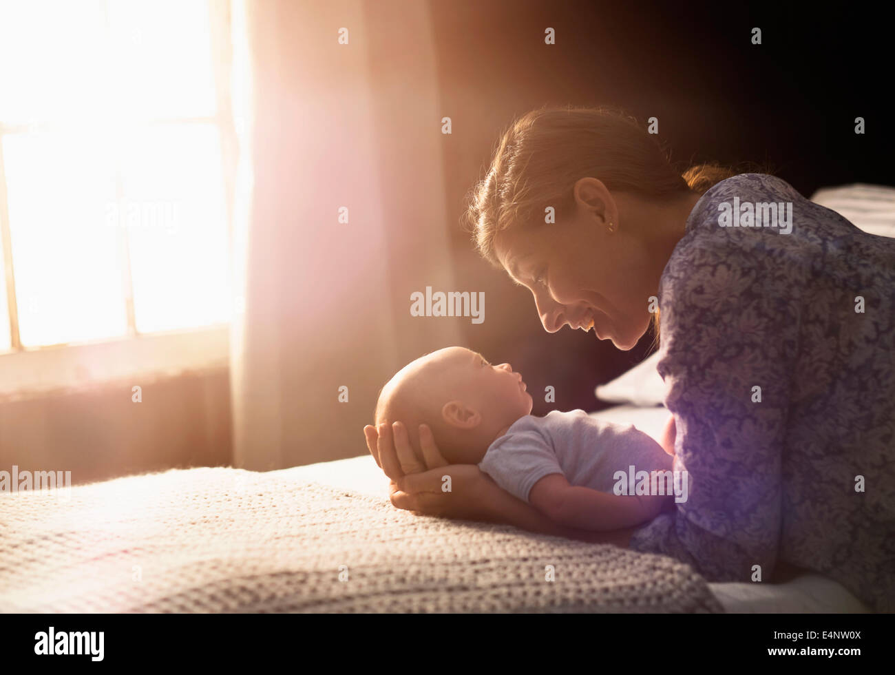 Mother holding baby boy (2-5 months) in bedroom - Stock Image